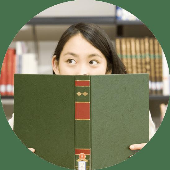 女の子が本で顔を隠している写真